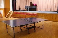 Silně poškozený pingpongový stůl vytažený ze zákulisí (v pozadí Ivoš Plhák opravuje a ladí klavír)